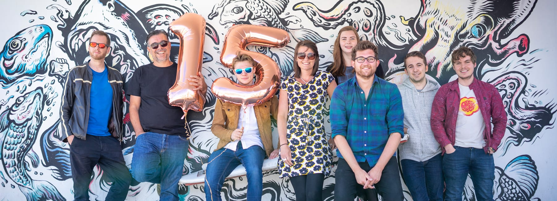 Digital Storm Team standing against a painted mural celebrating their anniversary with ballons